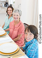 Multigeneration family sitting at dining table