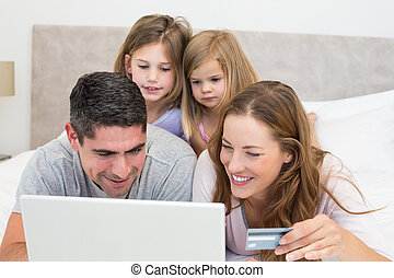 Family with credit card shopping online in bedroom