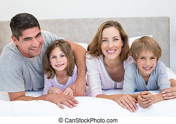 Family lying together in bed