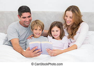 Family reading storybook - Smiling family reading storybook...