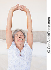Senior woman stretching on bed