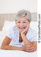 Happy senior woman lying in bed