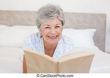 Happy senior woman reading story bo