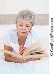 Senior woman reading story book in bed - Concentrated senior...