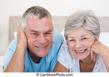 Senior couple smiling in bed - Portrait of senior couple...