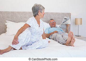 Senior couple relaxing in bed at home
