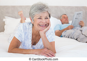 Senior woman with man reading newspaper on bed - Thoughtful...