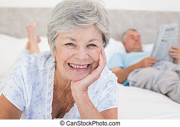 Senior woman with man in bed