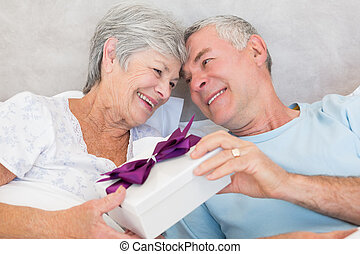 Senior couple exchanging gift box in bed - Happy senior...