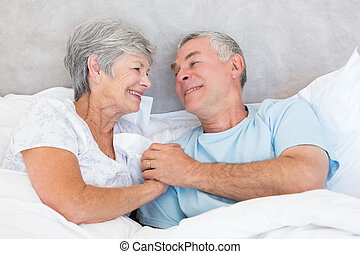 Senior couple holding hands in bed - Romantic senior couple...