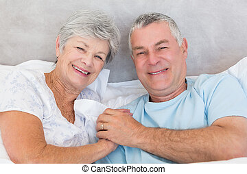 Happy senior couple holding hands in bed - Portrait of happy...