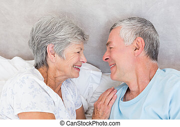 Smiling senior couple in bed - Smiling senior couple looking...