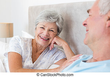 Happy senior woman with man in bed