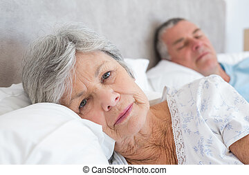 Senior woman lying with man in background - Portrait of sad...