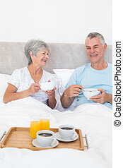 Senior couple having breakfast in bed - Happy senior couple...