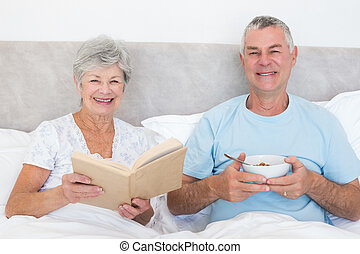 Senior couple with book and bowl in bed - Portrait of happy...