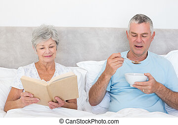 Senior couple with book and cereal bowl in bed