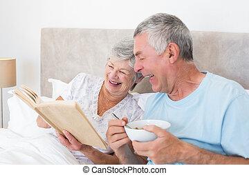 Senior couple reading book in bed - Happy senior couple...
