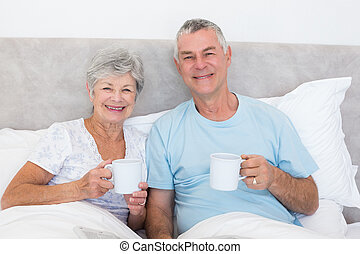 Senior couple holding coffee cups in bed - Portrait of...