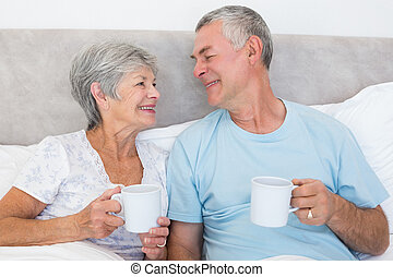 Senior couple with coffee cups in bed - Senior couple with...