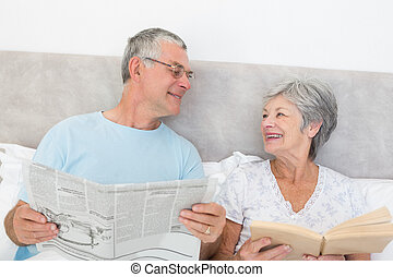 Senior couple with newspaper and book in bed - Senior couple...