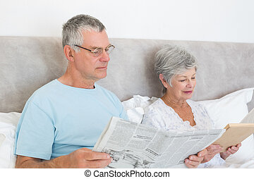 Senior couple with newspaper and book in house - Senior man...