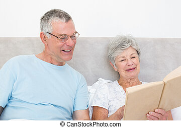 Senior couple reading book together in bed