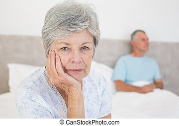 Disappointed senior woman with husband in background -...
