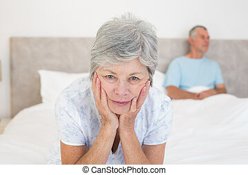 Sad senior woman with husband in bed