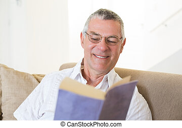 Senior man reading book on sofa