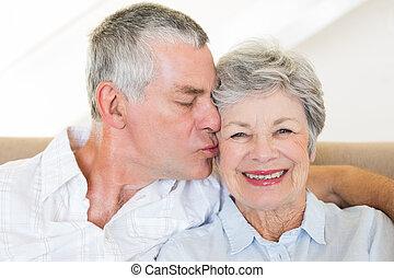 Senior man kissing wife on cheeks