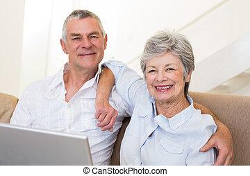 Senior couple with laptop on sofa