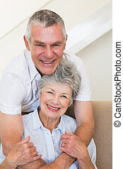 Senior man embracing wife on sofa