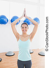 Beautiful woman with joined hands in fitness studio -...