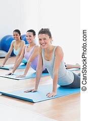 Smiling class doing the cobra pose in fitness studio -...