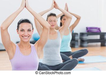 Women with joined hands at fitness studio - Sporty young...