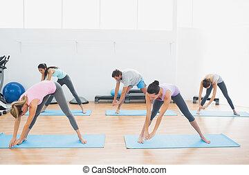 Sporty class doing pilate exercises in fitness studio - Full...