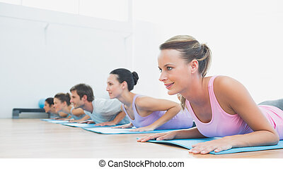 Class exercising in row at fitness studio - Side view of a...