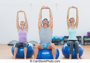 Sporty people stretching up hands on exercise balls at gym -...