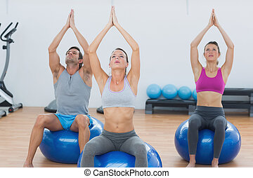 People with joined hands on exercise balls in gym - Sporty...