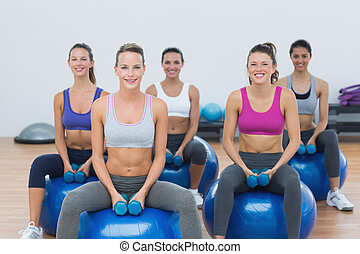 Women exercising with dumbbells on fitness balls - Smiling...