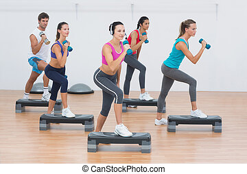 Fitness class performing step aerobics exercise with...
