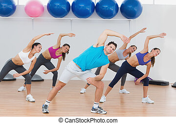 Class doing stretching exercise in fitness studio -...