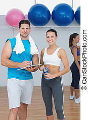 Couple with a woman in background at the gym