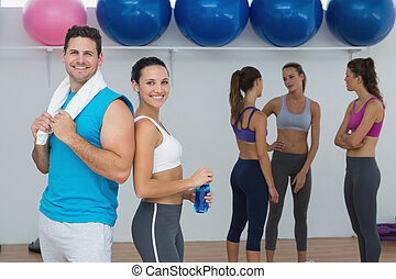 Smiling couple with fitness class in background - Portrait...