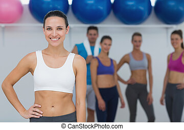 Female instructor with fitness class in background