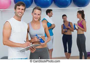 Couple holding clipboard with fitness class in background -...