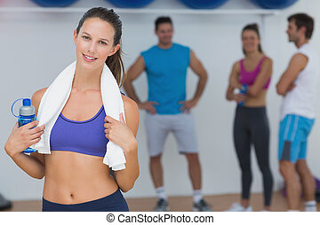 Portrait of a fit female holding water bottle with fitness class in background at gym