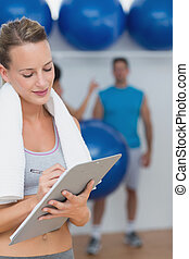 Female trainer writing on clipboard with fitness class in...