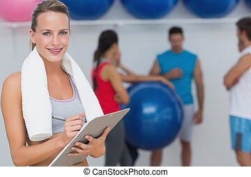 Portrait of a female trainer holding clipboard with fitness...